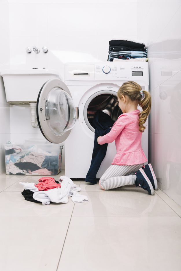 young girl putting in laundry