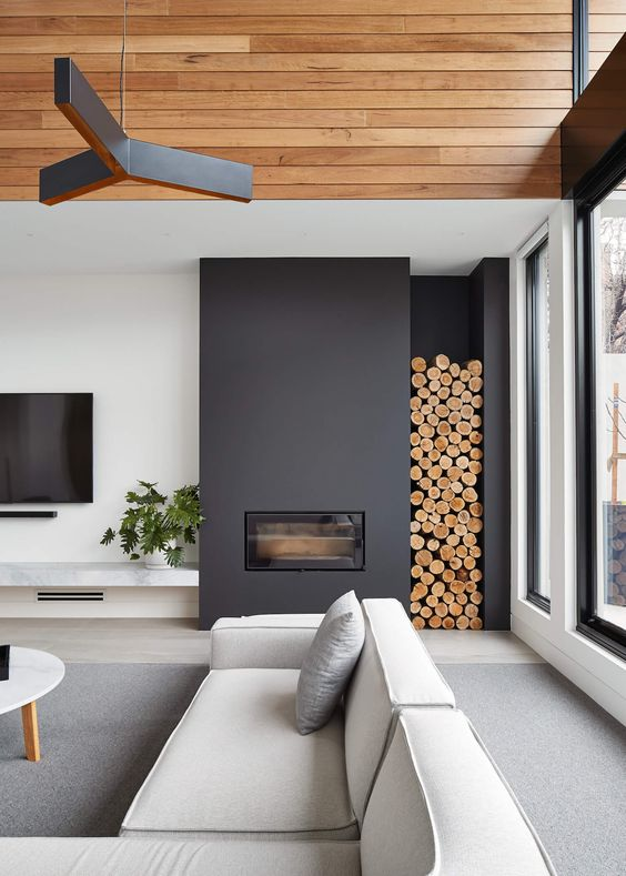 modern asymmetrical fireplace with wood stack